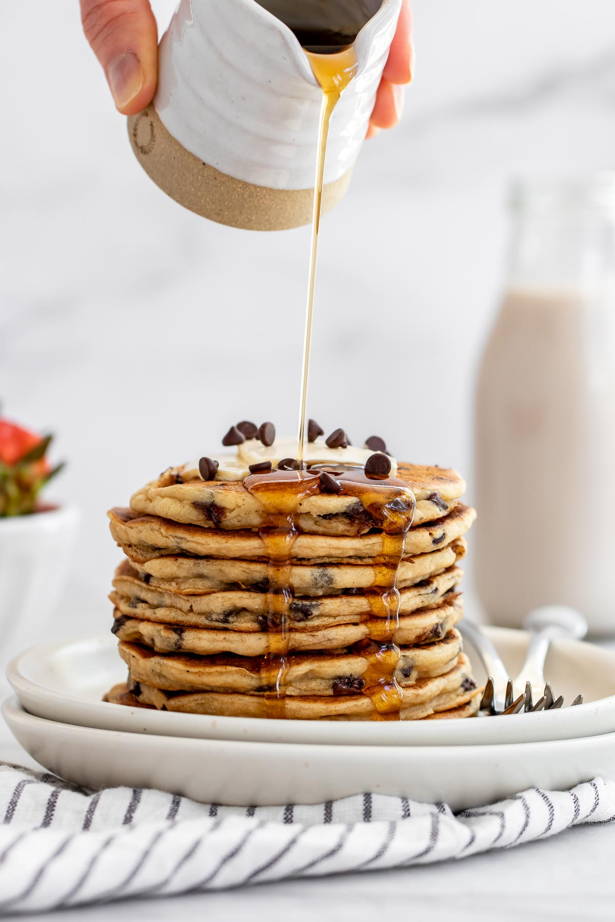 Pouring maple syrup over the gluten free pancakes with a pitcher.