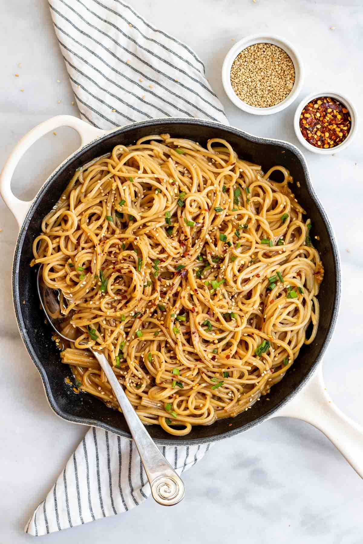 Skillet with the noodles and a large spoon on the side.