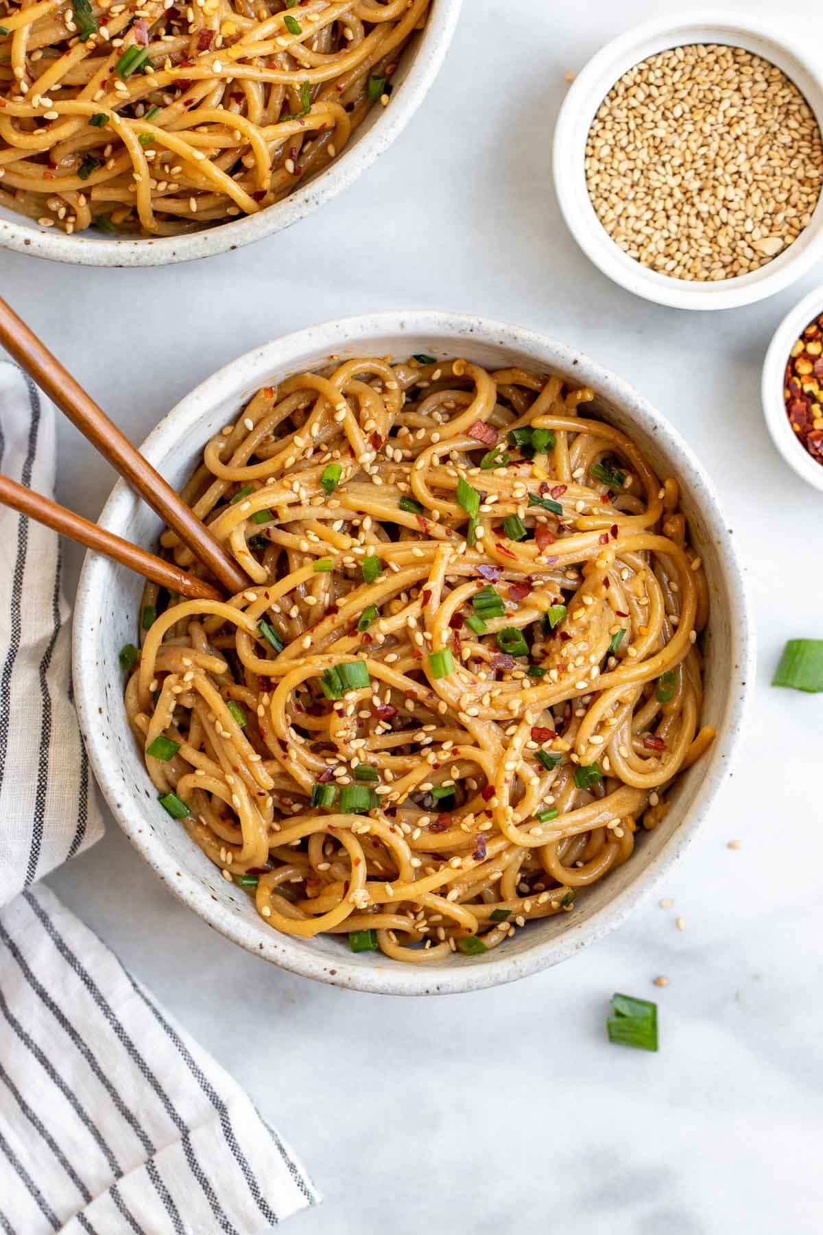 Two bowls with the sesame noodles with chives on top.