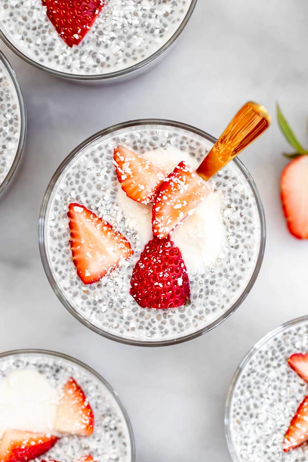 Overhead shot of coconut chia pudding with strawberries and yogurt on top.