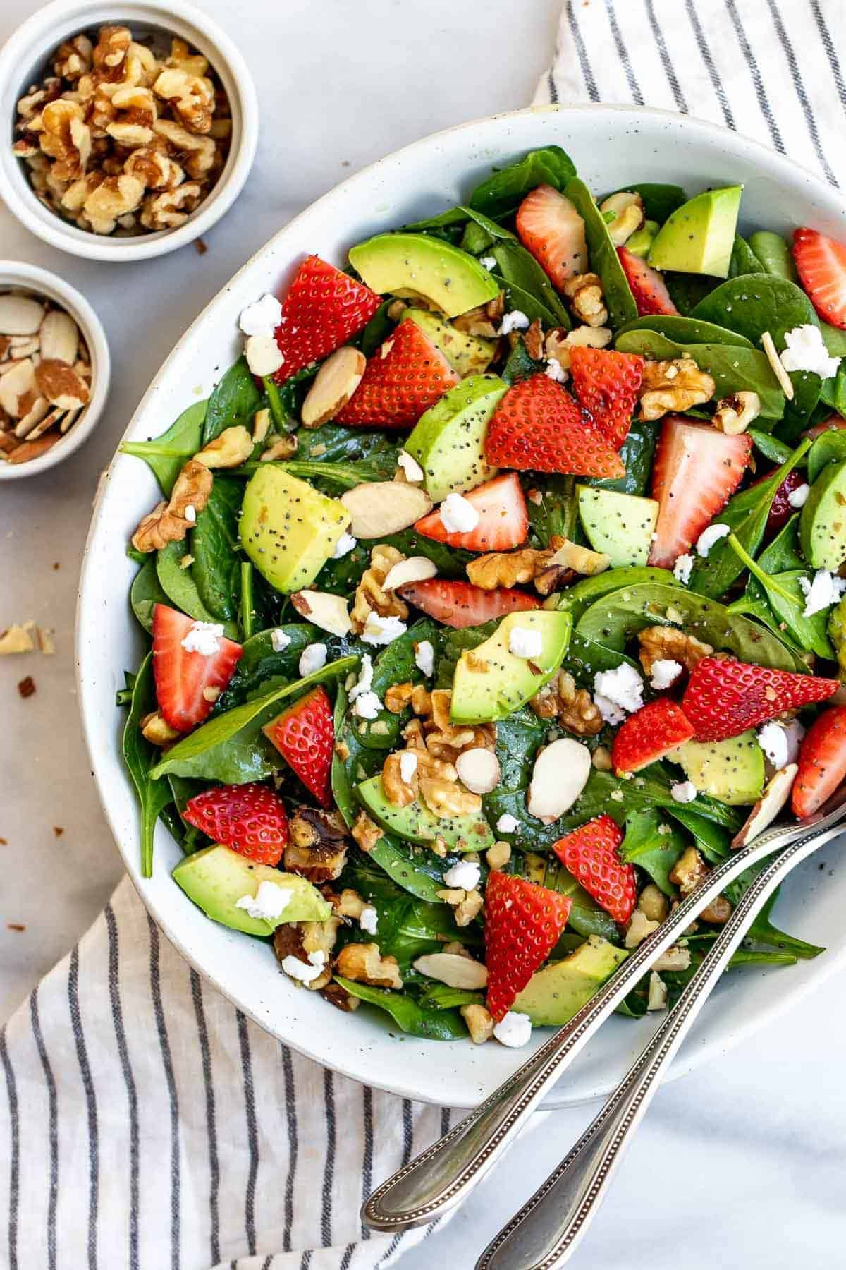 Close up of the final spinach salad with fresh strawberries and avocado.