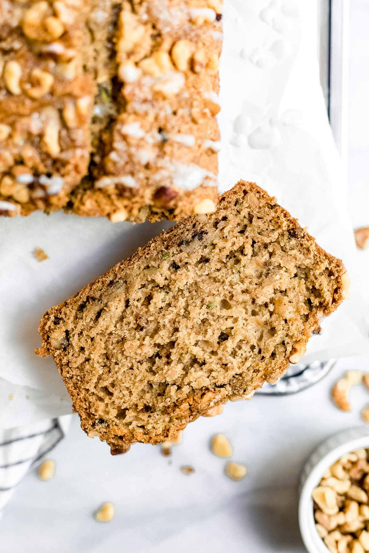 Up close image of the zucchini bread with one slice on the side to show texture.