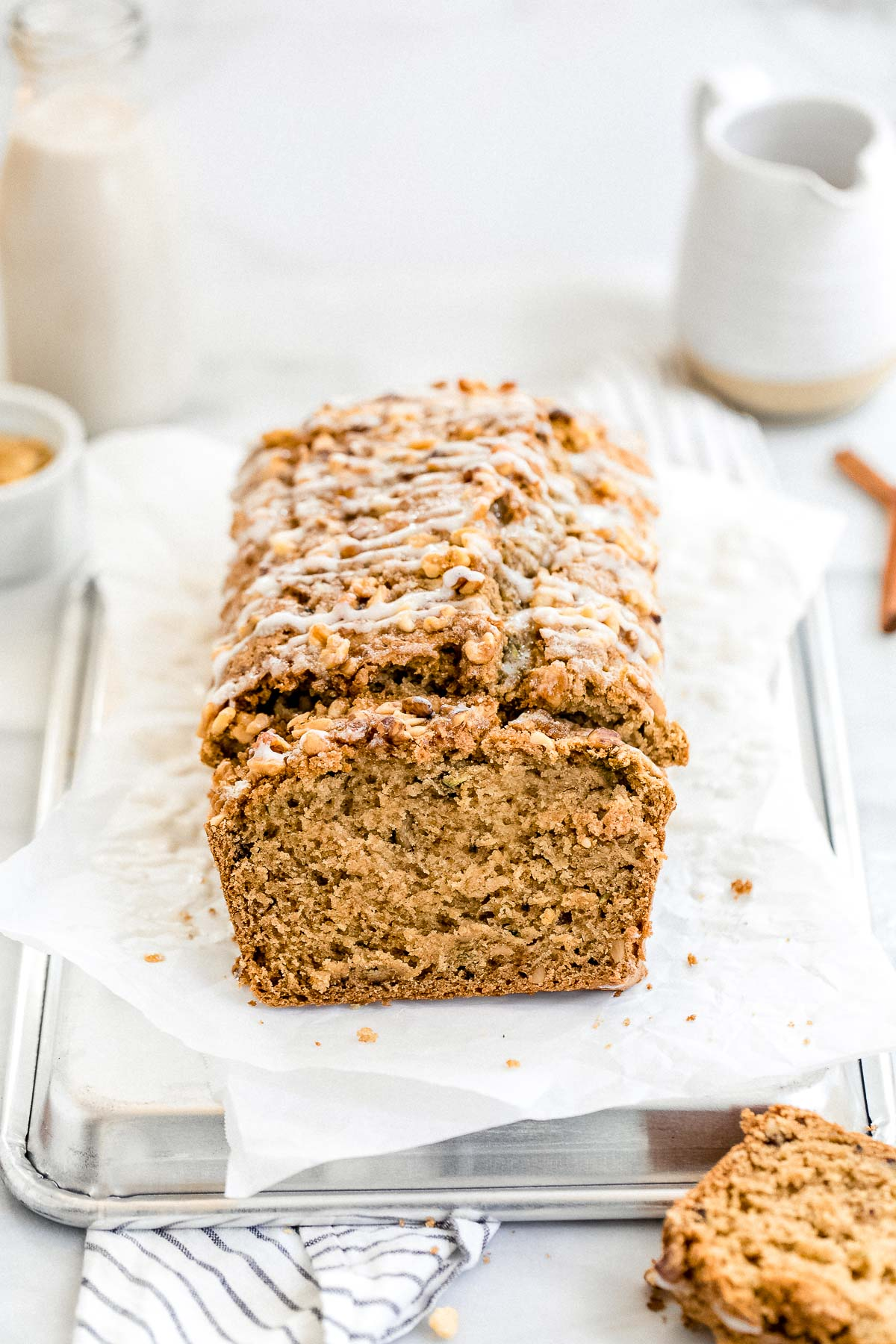 Gluten free zucchini bread with a drizzle on top with milk in the background.