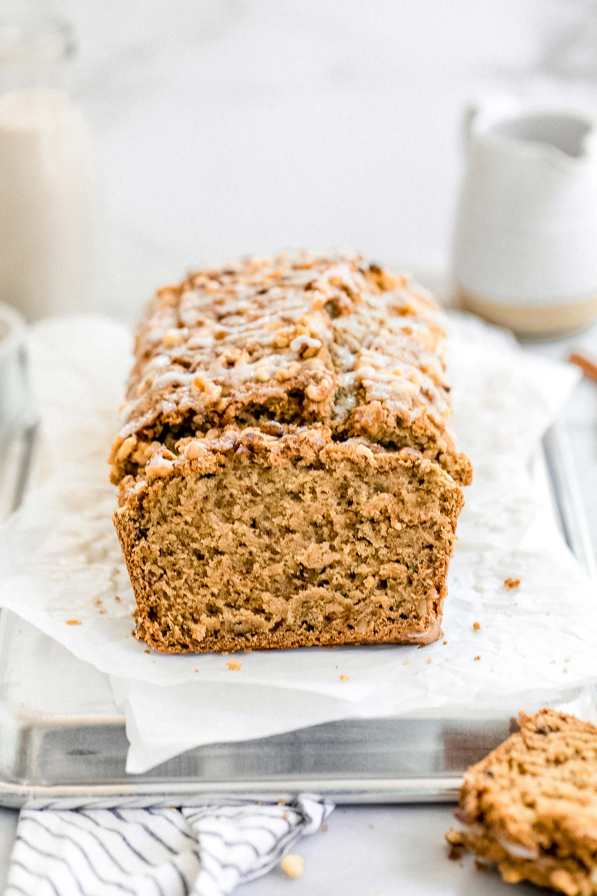 Gluten free zucchini bread with chopped walnuts on top sitting on parchment paper.