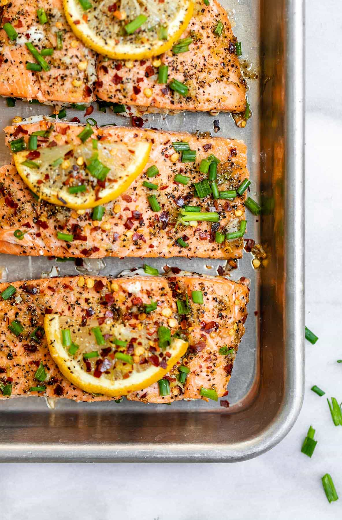 Final baked salmon on a baking sheet with lemon wedges on top.