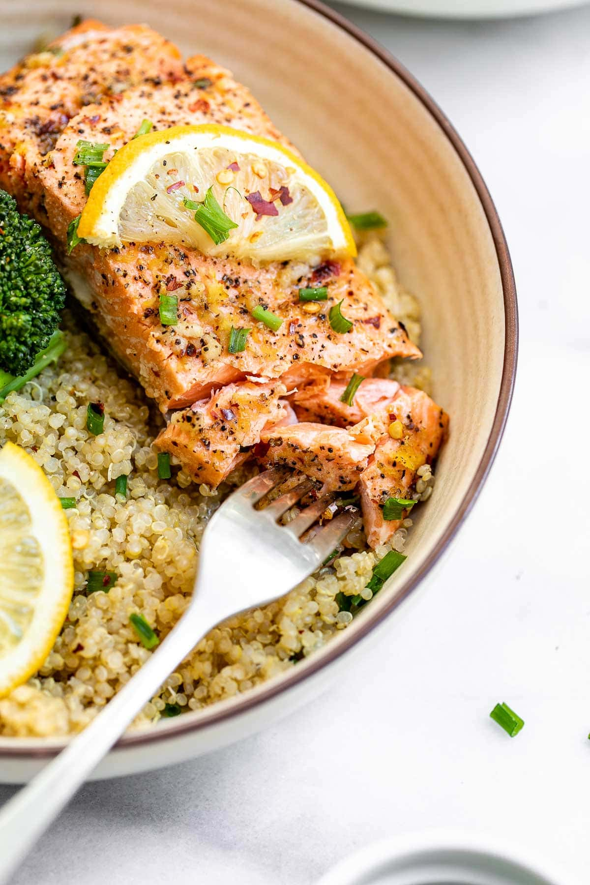 Up close image of the lemon pepper salmon with a fork taking a bite.
