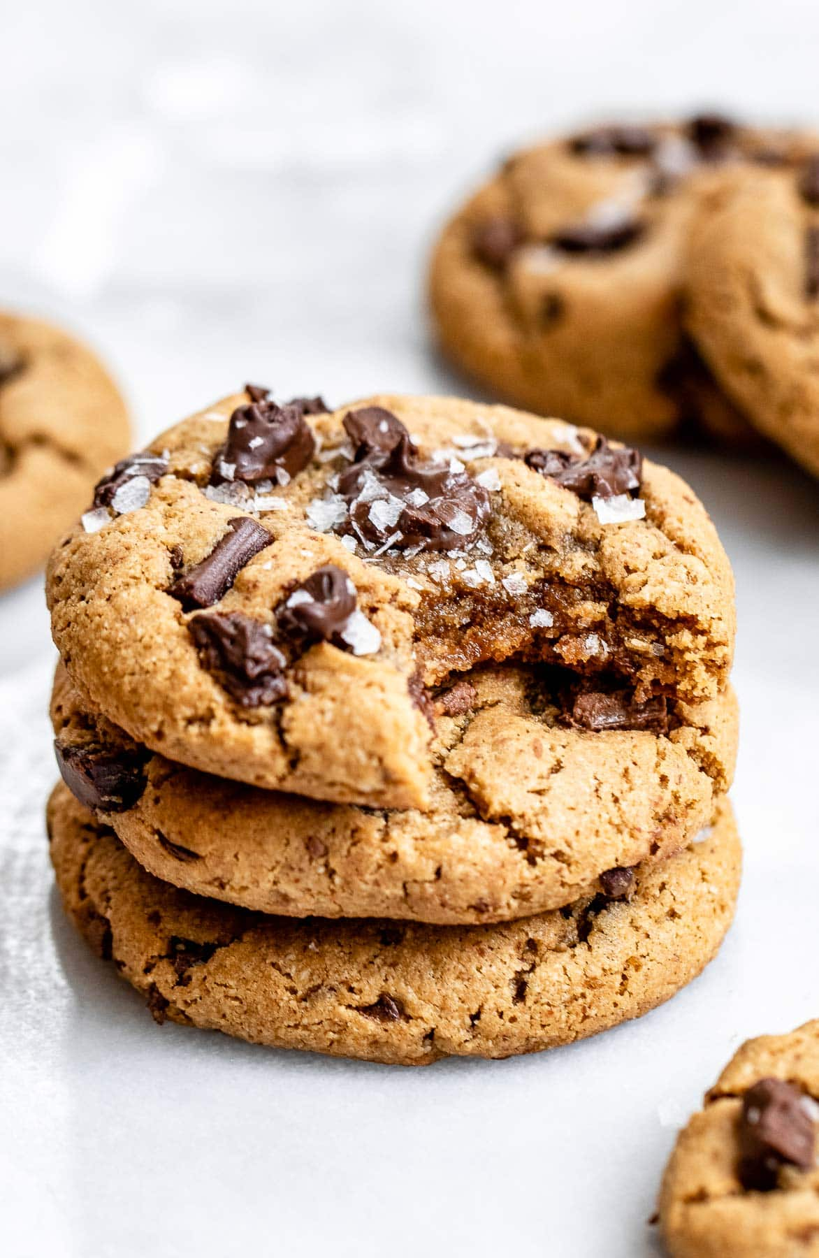 Three chocolate chunk cookies stacked on top of each other.