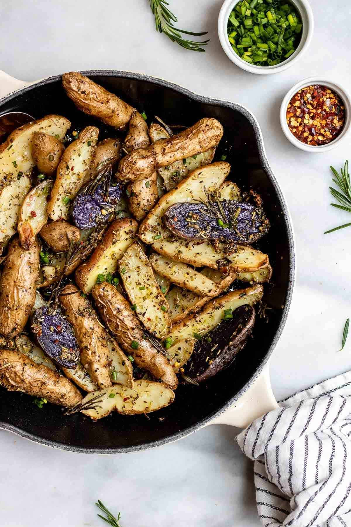Roasted fingerling potatoes in a cast iron skillet with a towel on the handle.