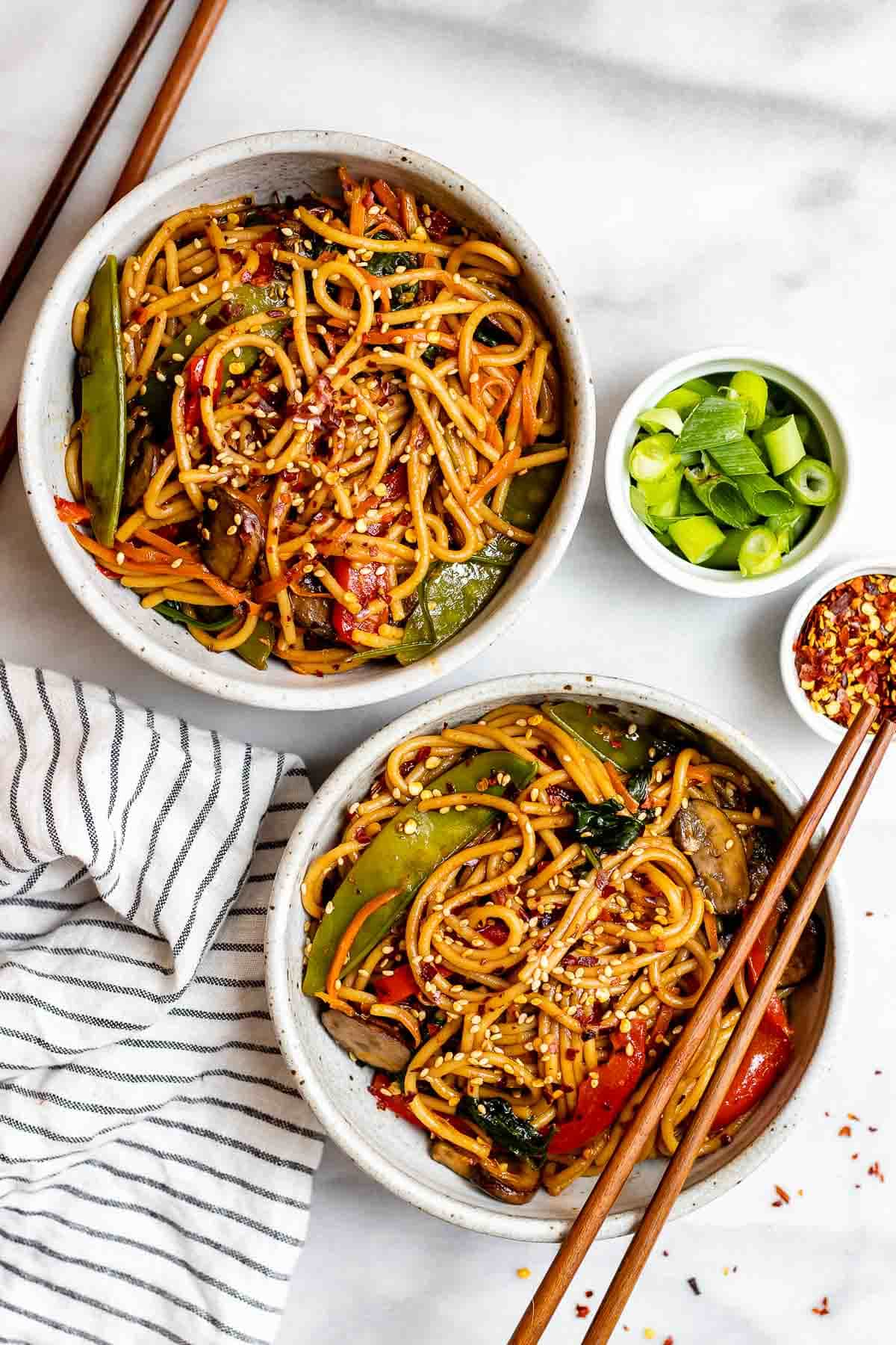 Two bowls with lo mein and sesame seeds on top.