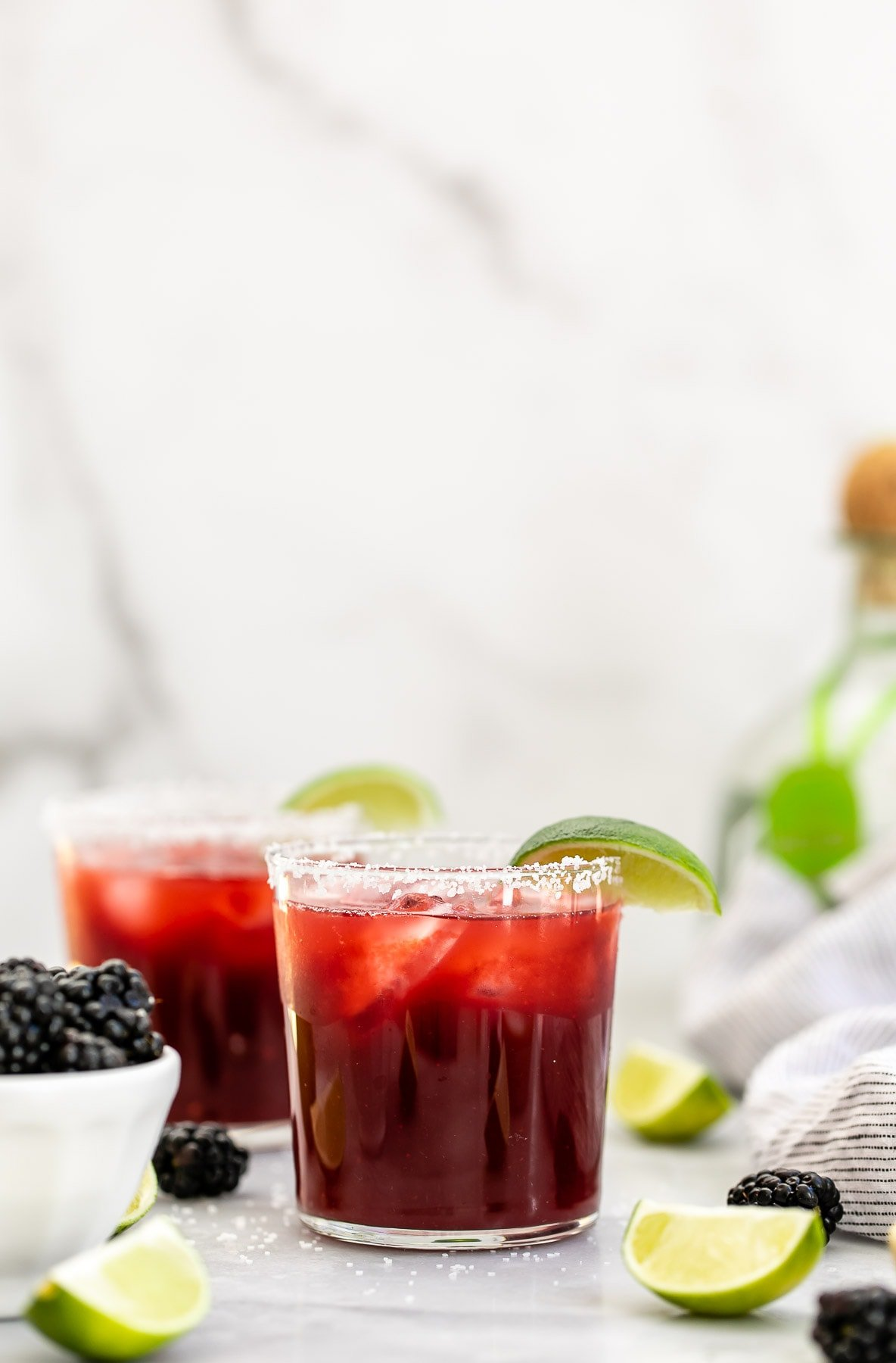 Blackberry margarita in a glass with lime wedges.