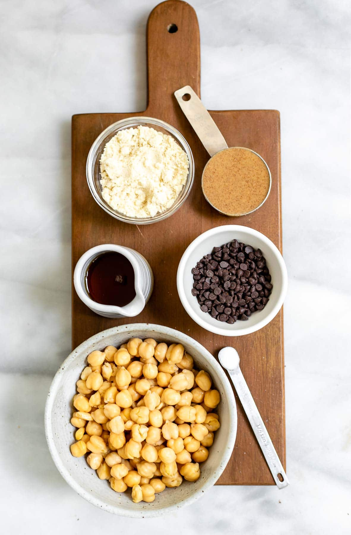 Ingredients for the chickpea cookie dough arranged in bowls on a wood board.