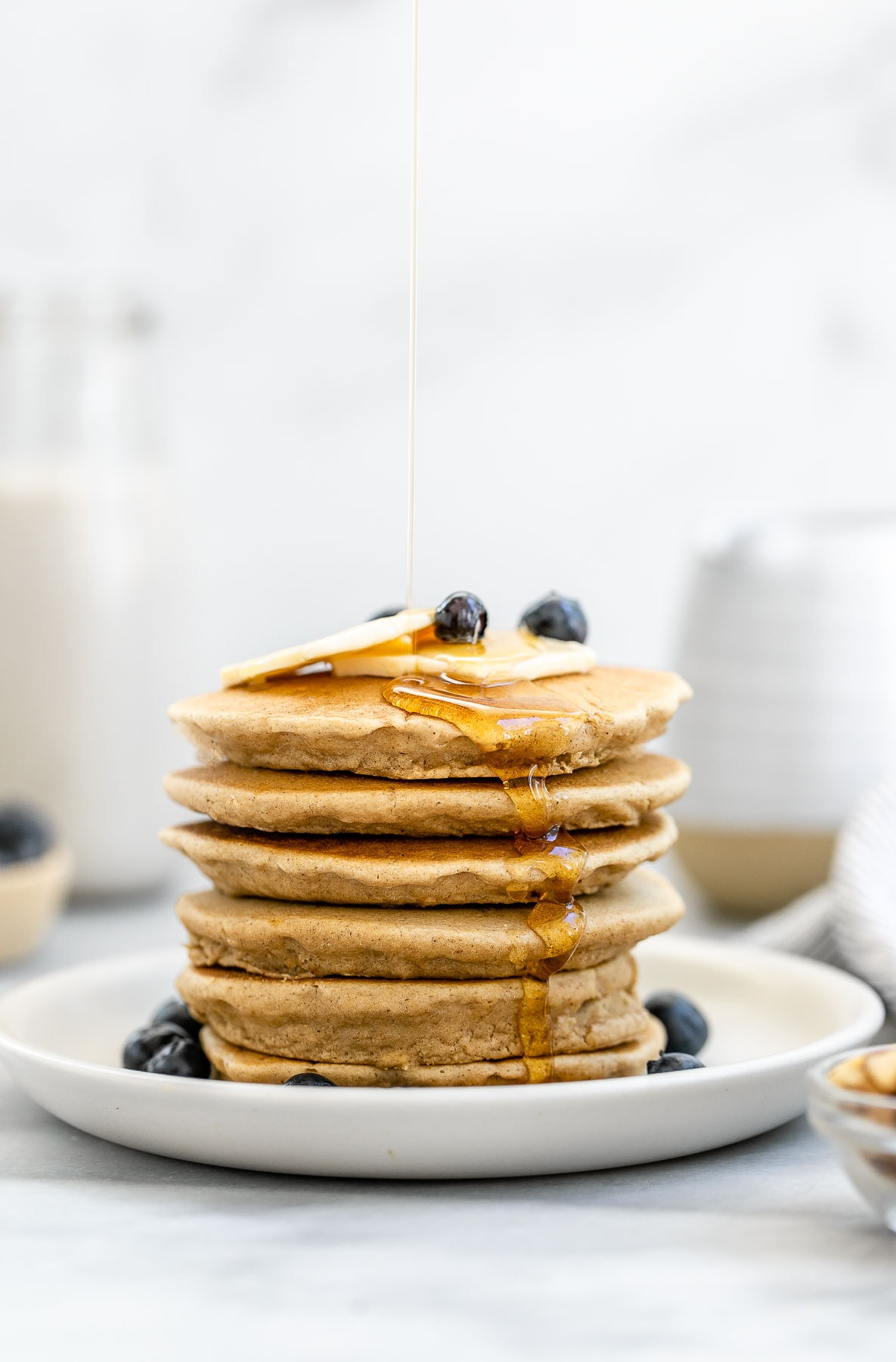 Oat flour pancakes stacked on each other with maple syrup pouring down the side.