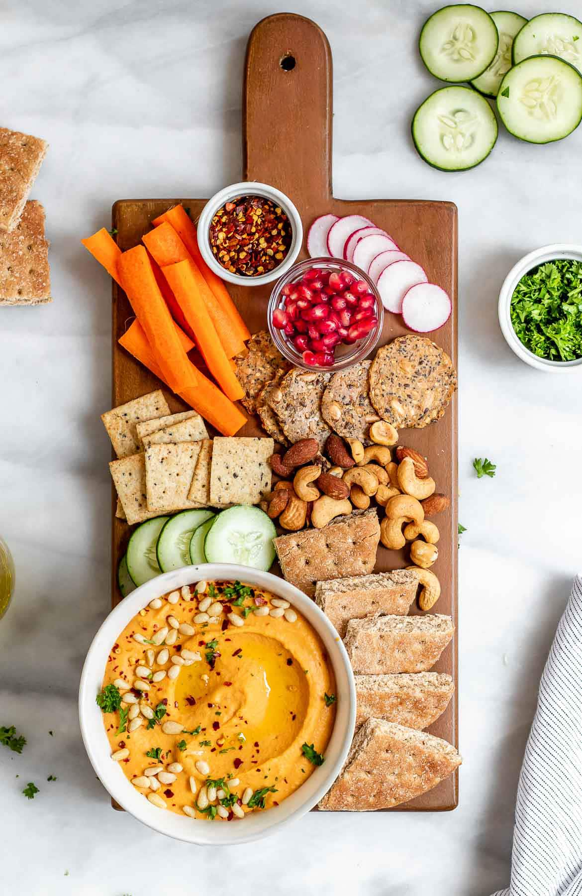 Cheese board with crackers, veggies, nuts and the roasted red pepper hummus.