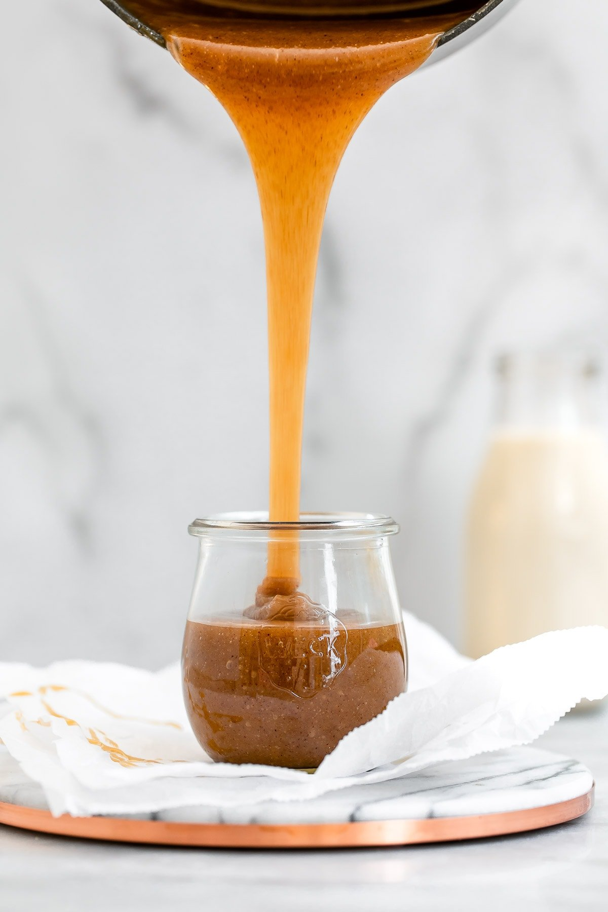 Pouring the caramel into a glass jar from a black pot.
