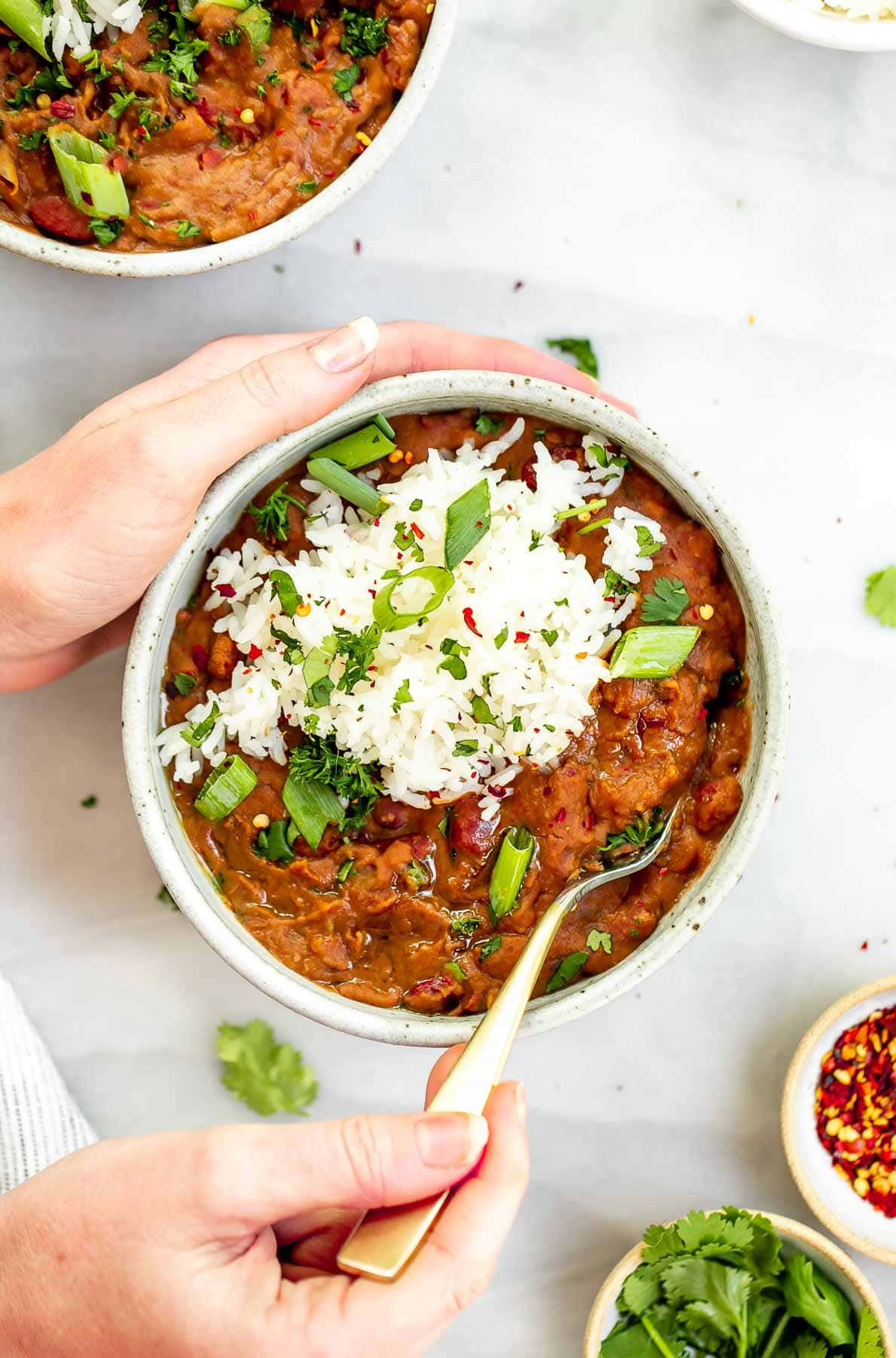 Hands holding onto a bowl of the red beans and rice with a spoon on the side.