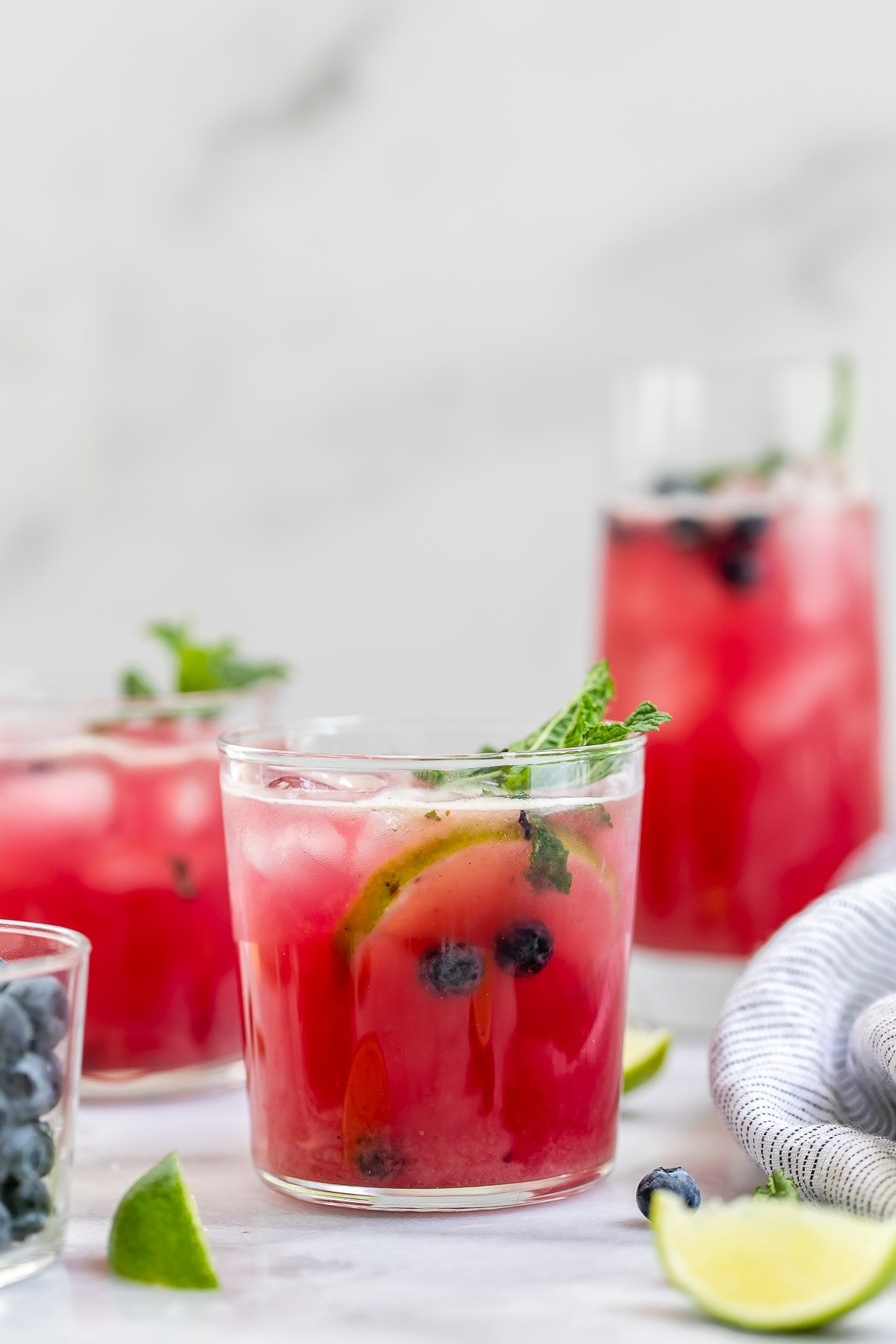 Three glasses with the blueberry mojito with lime wedges.