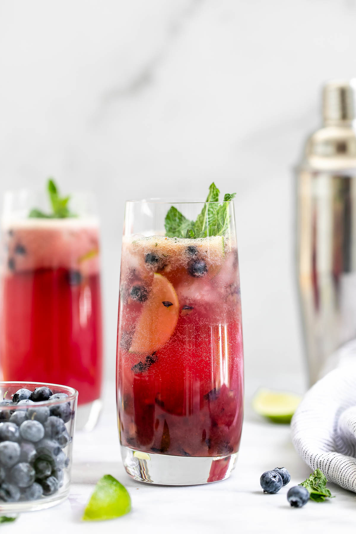 Two highball glasses with the blueberry mojito with mint and lime.