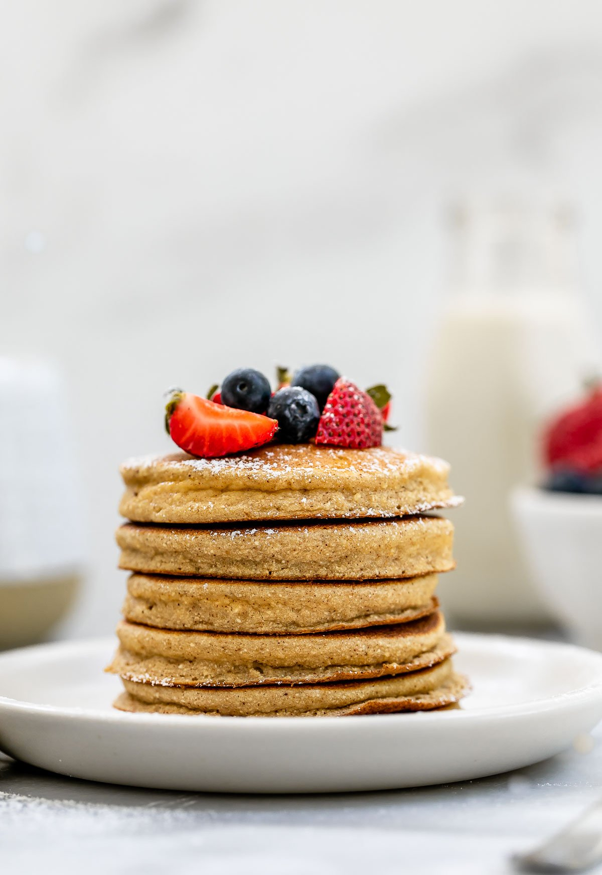 Coconut flour pancakes stacked on a plate with berries on top.