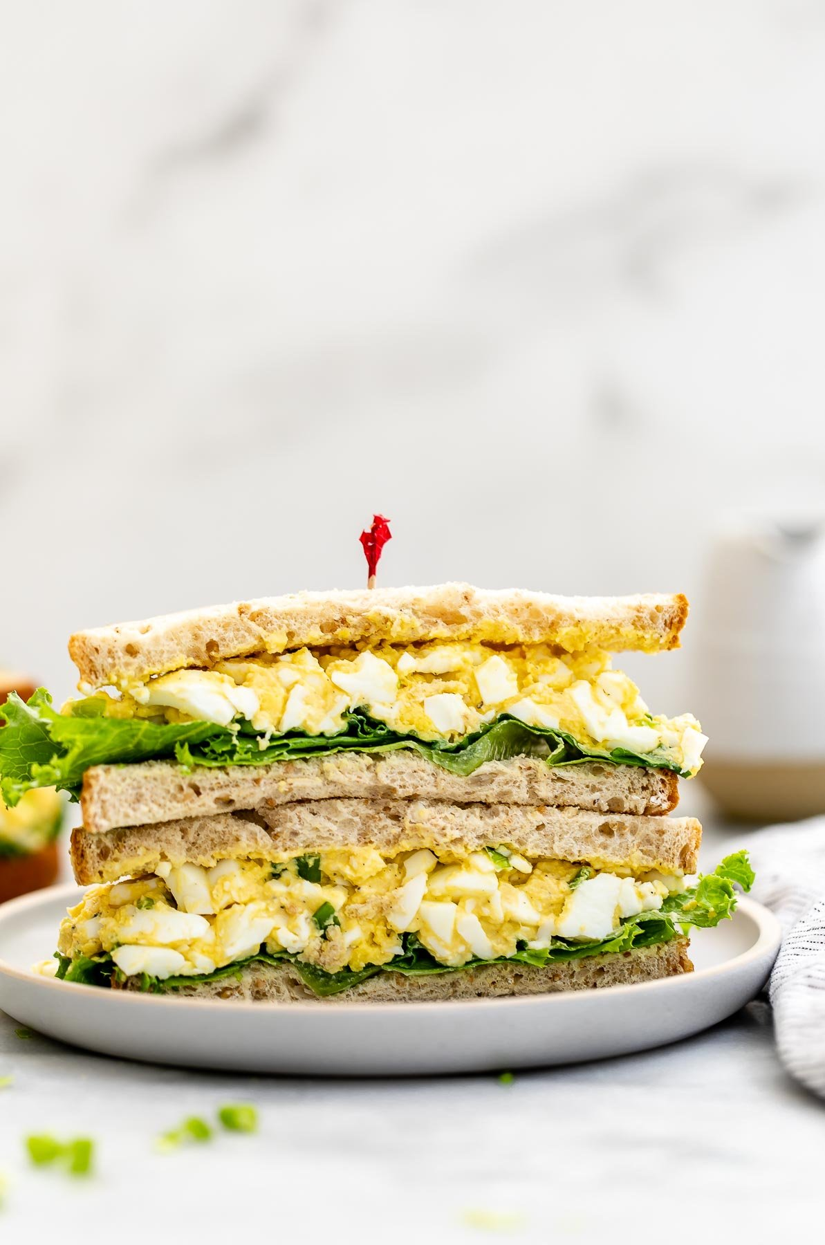 Healthy egg salad sandwich cut in half on a small plate.