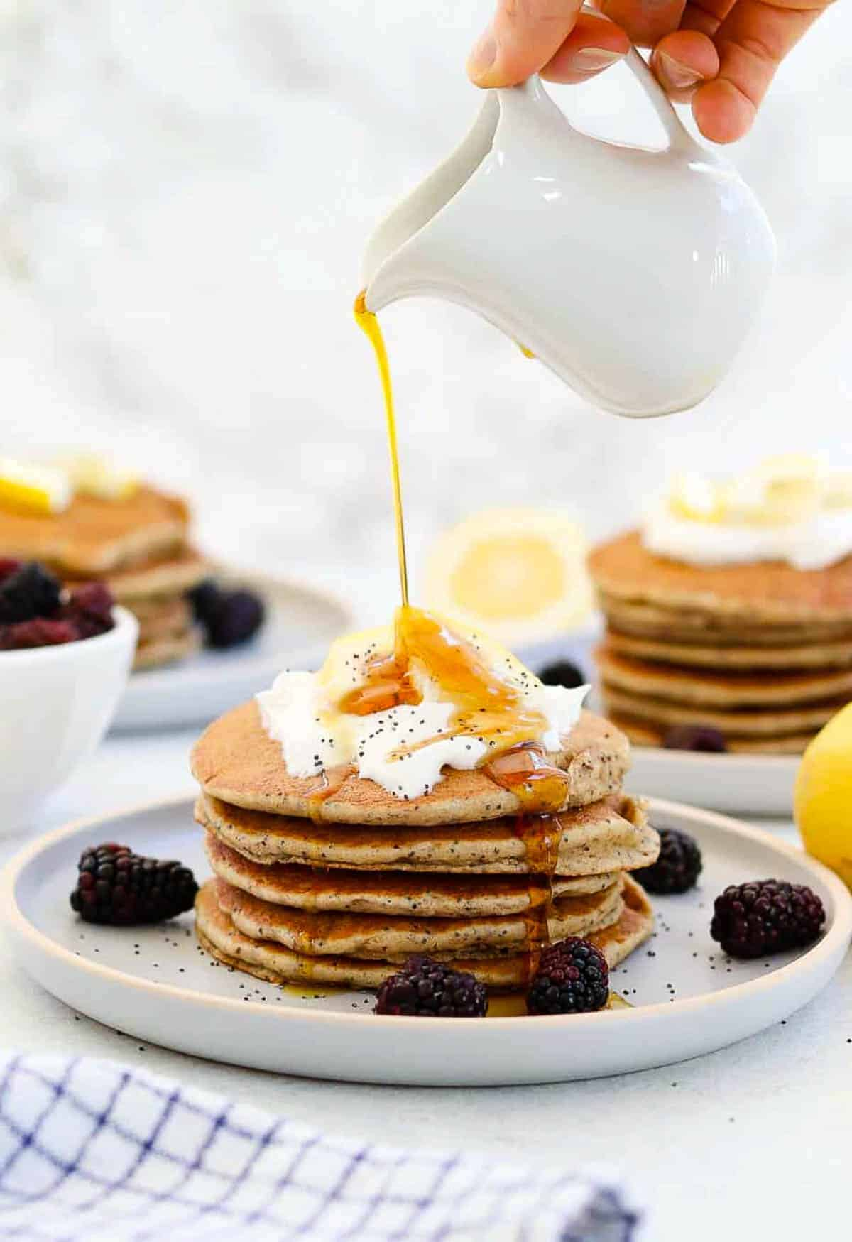 Stack of pancakes with coconut cream and maple syrup pouring on top.