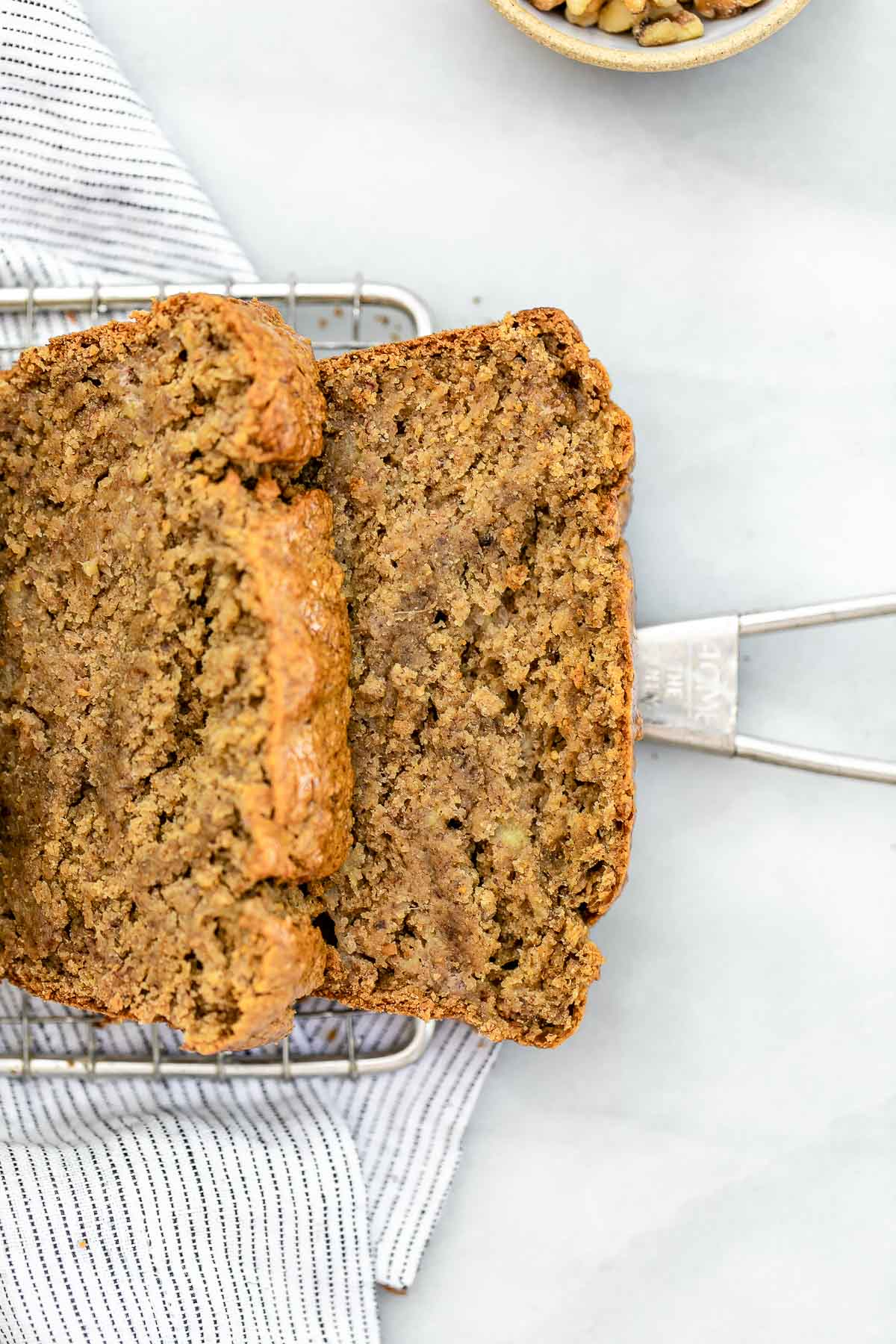 Two slices of gluten free banana bread lying on a cooling rack.