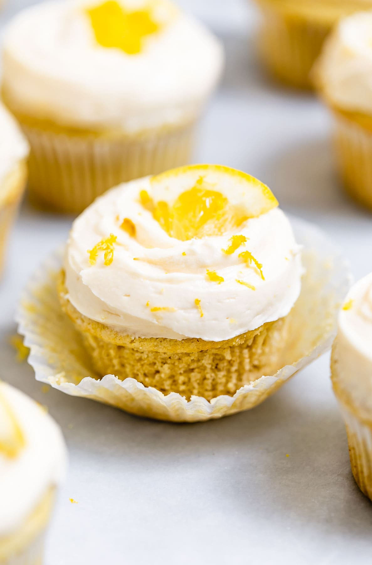 Vegan cupcakes arranged on a white backdrop with lemon wedges on top.