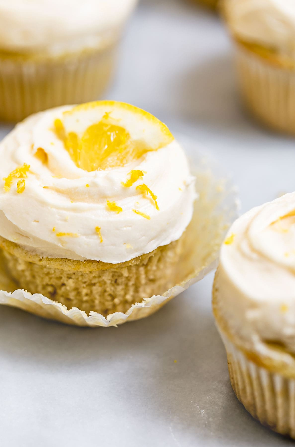 vegan lemon cupcake with the wrapper pulled off slightly.