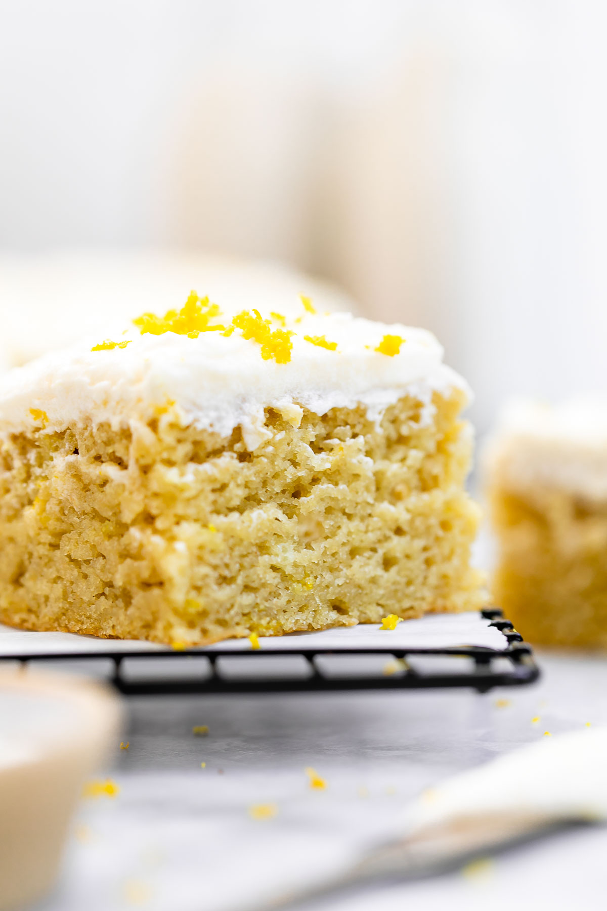 One slice of the lemon cake on a cooling rack.