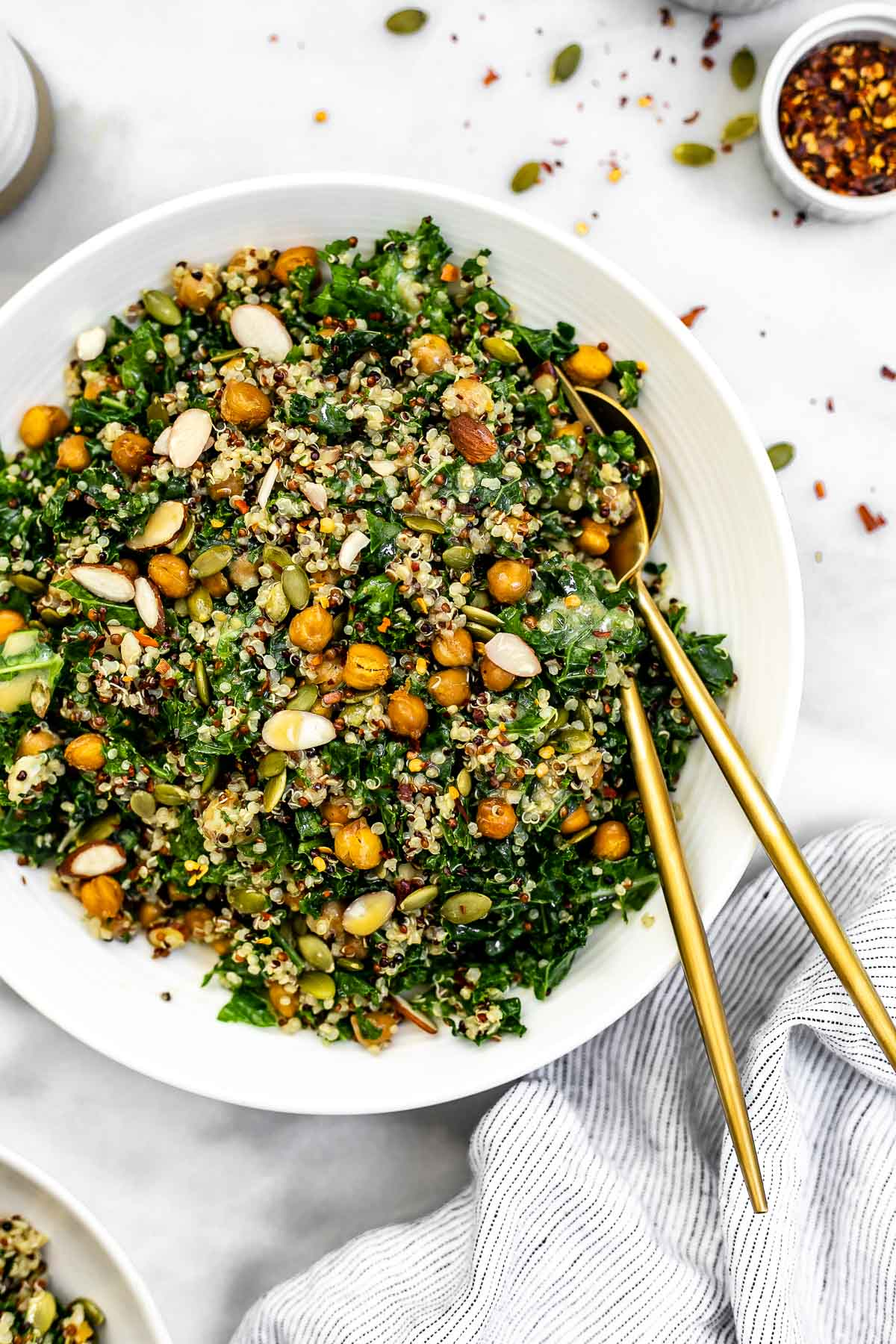 Kale quinoa salad with crispy garlic chickpeas in a white bowl.