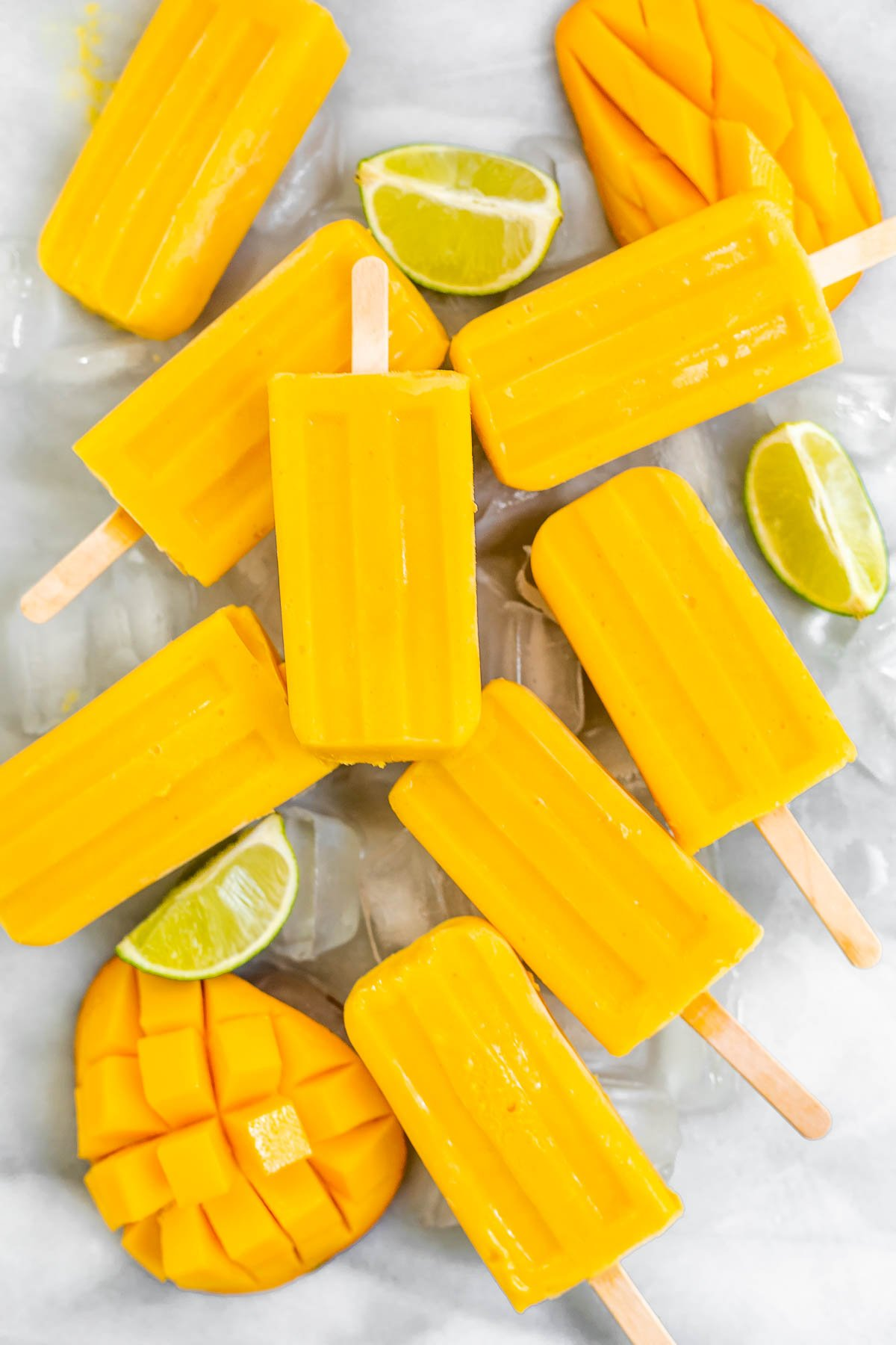 Mango popsicles with lime wedges over ice.