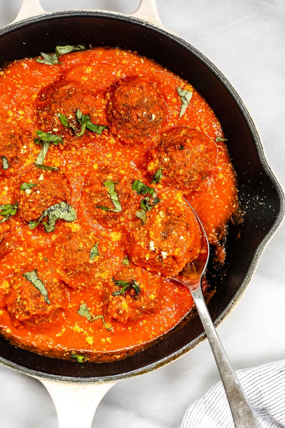 Vegan lentil meatballs coated in marinara in a large pan.