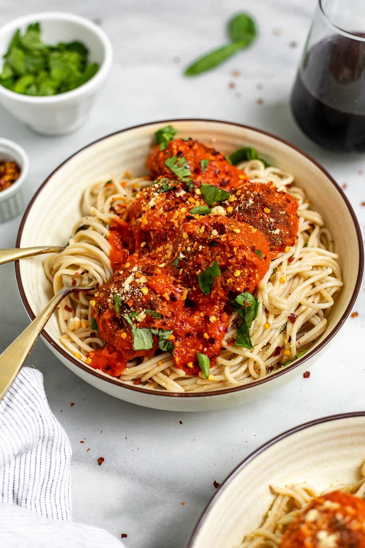 Angled view of the vegan lentil meatballs in a bowl with spaghetti.