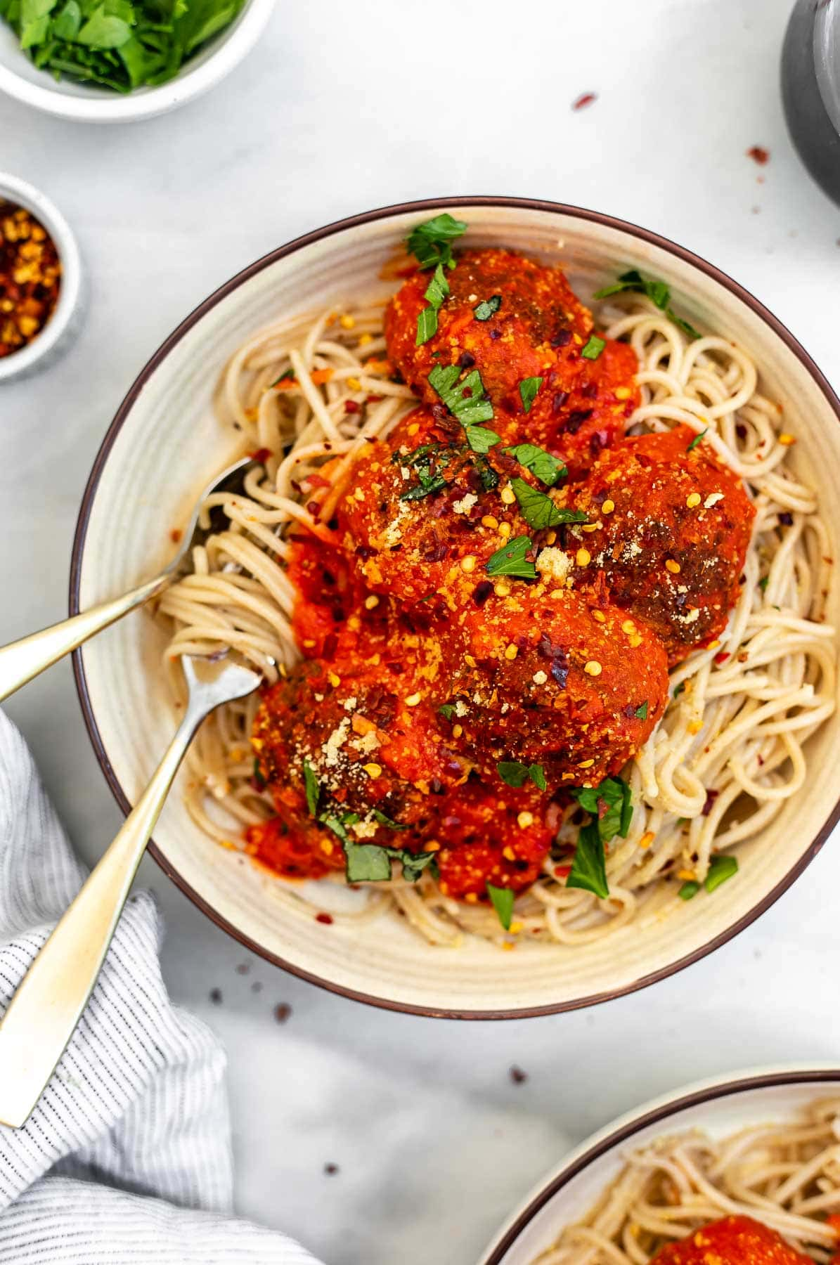 Vegan lentil meatballs with marinara sauce served over spaghetti.