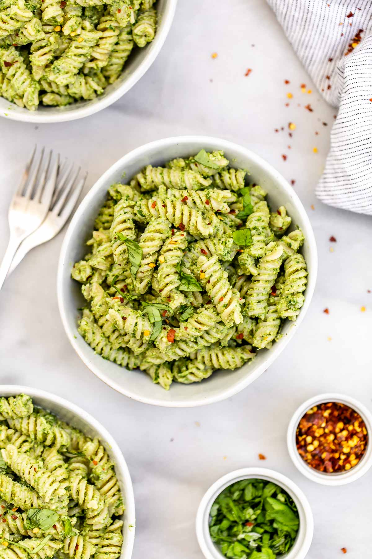 Vegan pesto pasta with fresh basil in a white bowl.