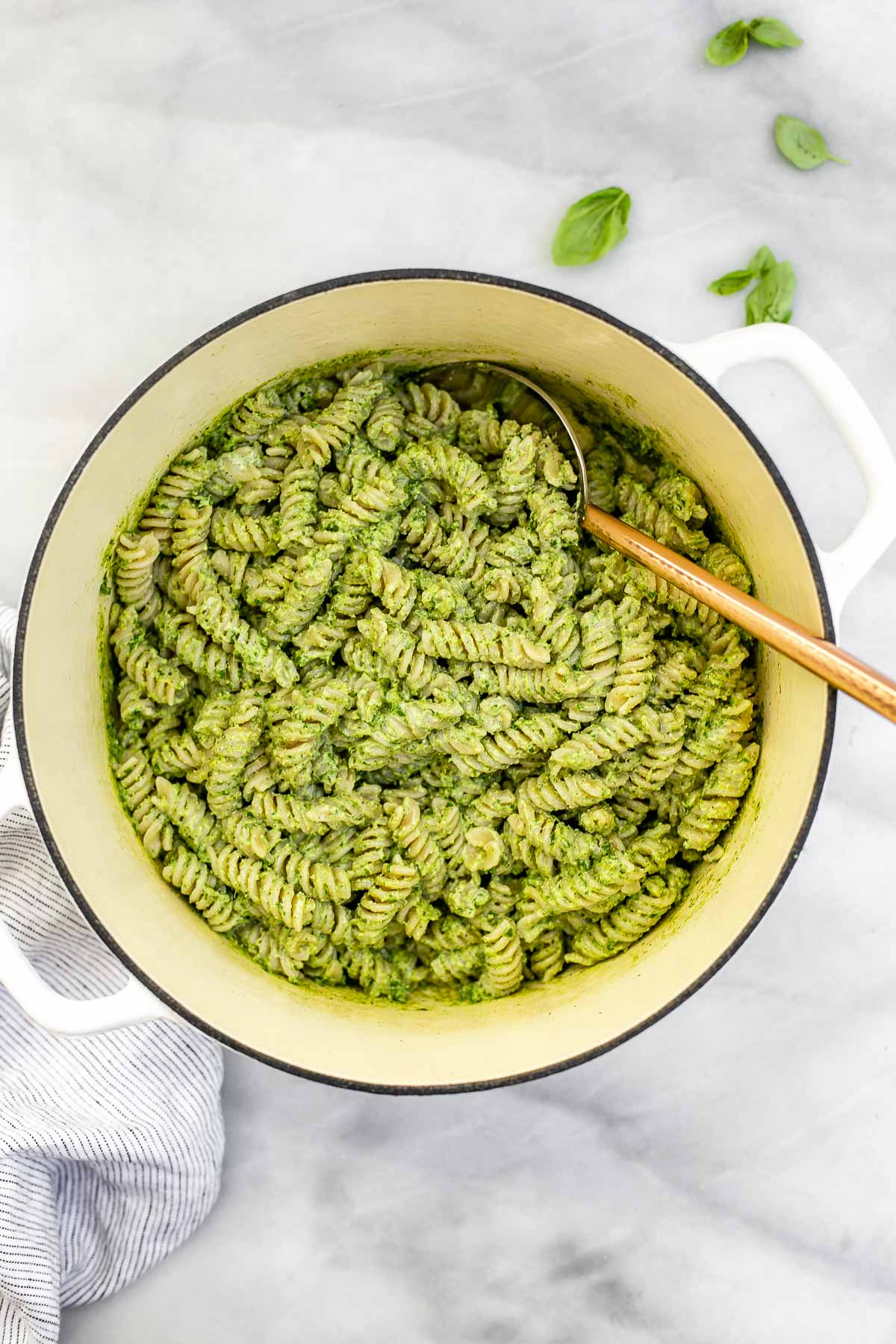 Vegan pesto pasta in a large white pot.