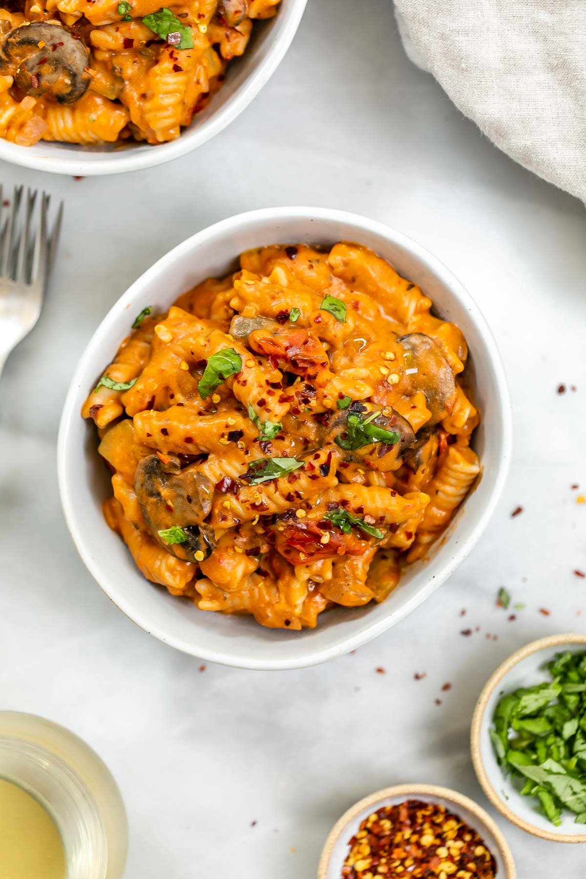 Vegan one pot pasta in a bowl with fresh basil on top.