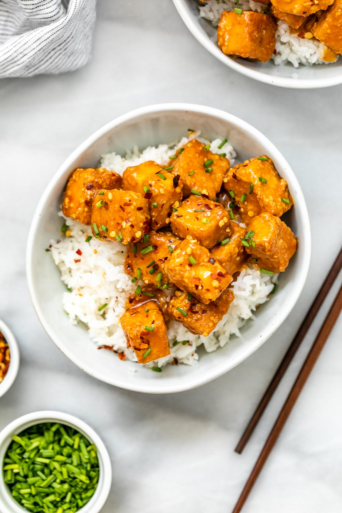 Baked orange tofu in a small bowl with chopsticks.