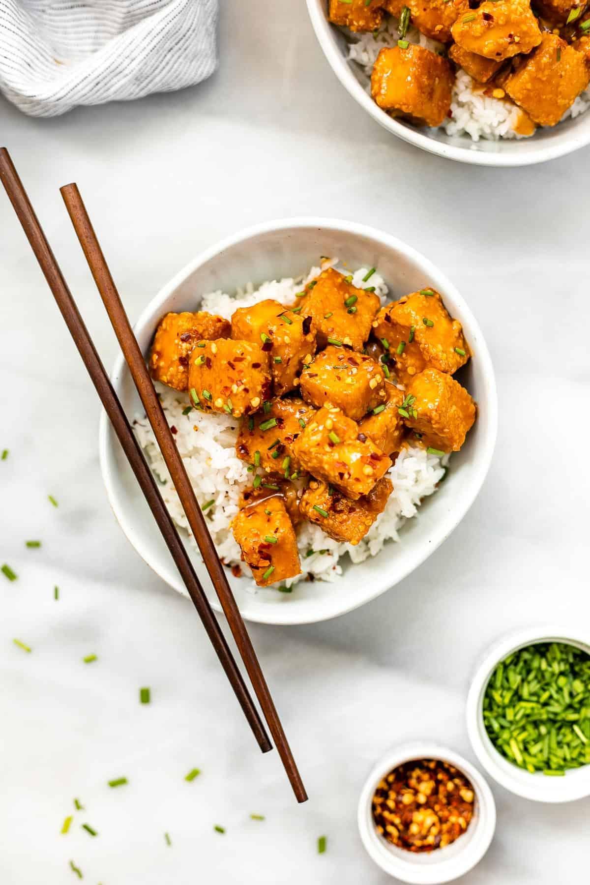 Baked crispy tofu with chopsticks.