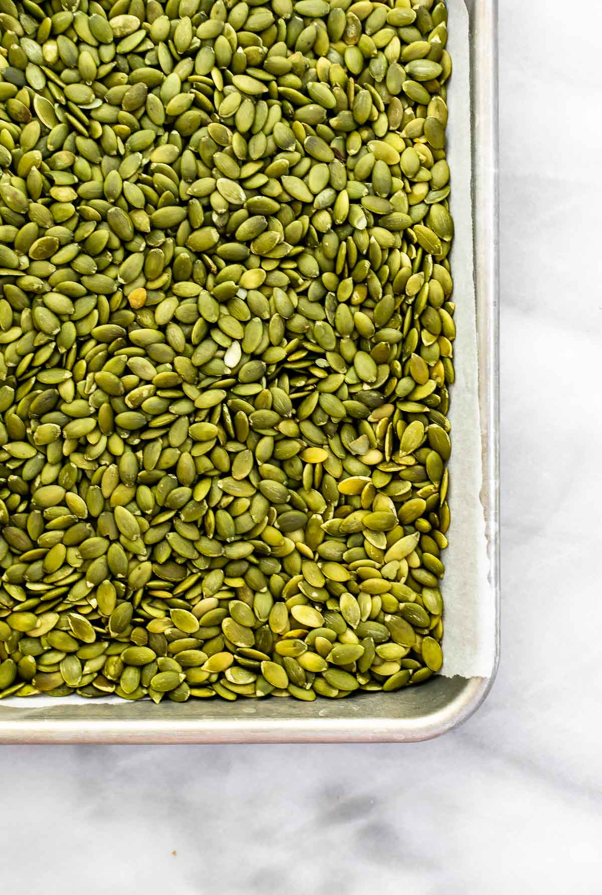 Pumpkin seeds on a baking tray.