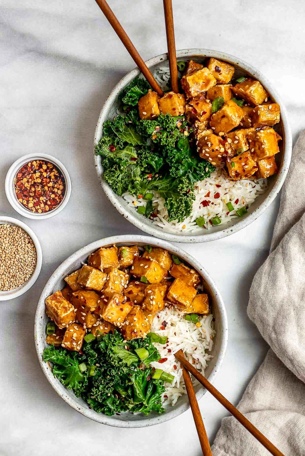 two bowls with teriyaki tofu with steamed kale and white rice.