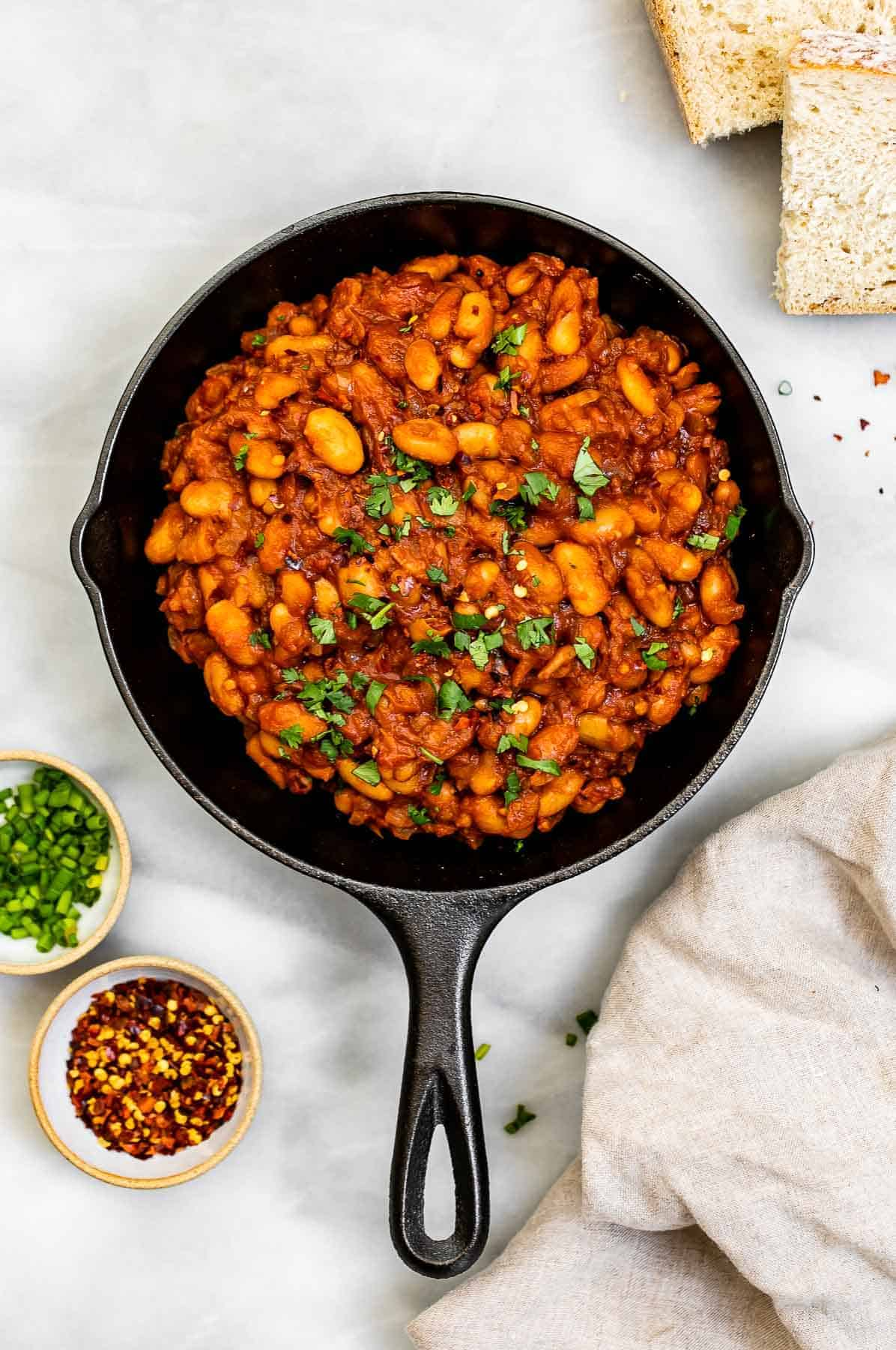 Vegan baked beans in a black pan with bread on the side.