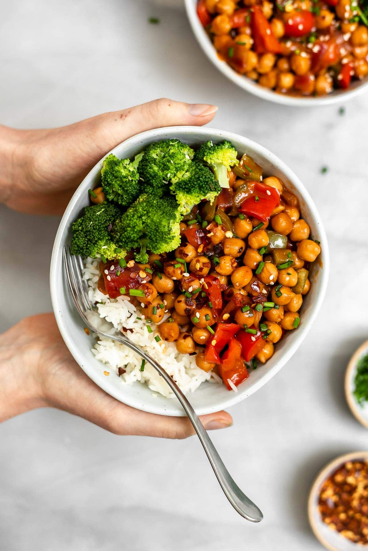 General tso's chickpeas with hands holding the bowl.