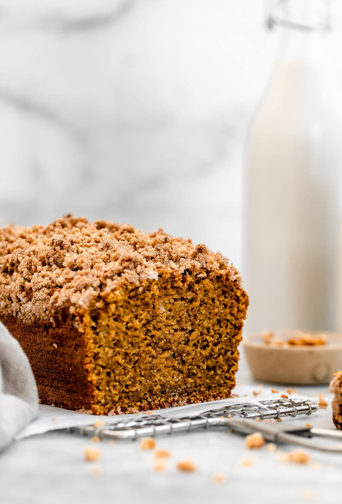 Healthy pumpkin bread with a jar of  milk in the back.
