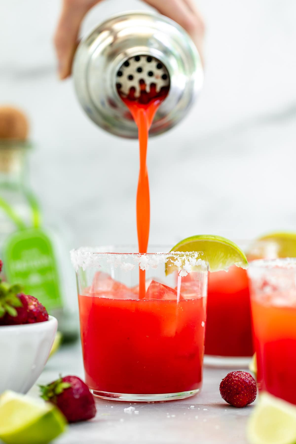 Pouring the margarita into three glasses.