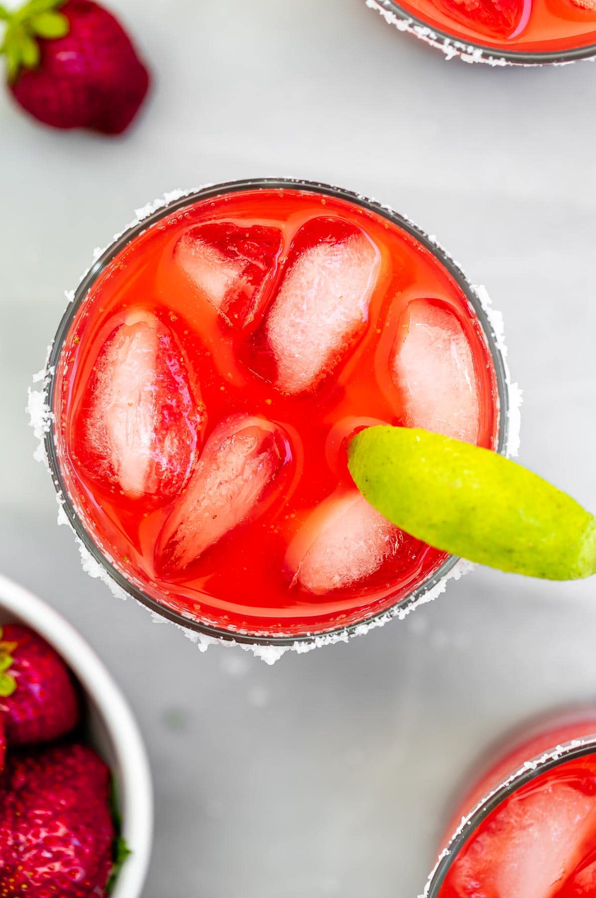 Overhead shot of strawberry margarita with lime wedges.