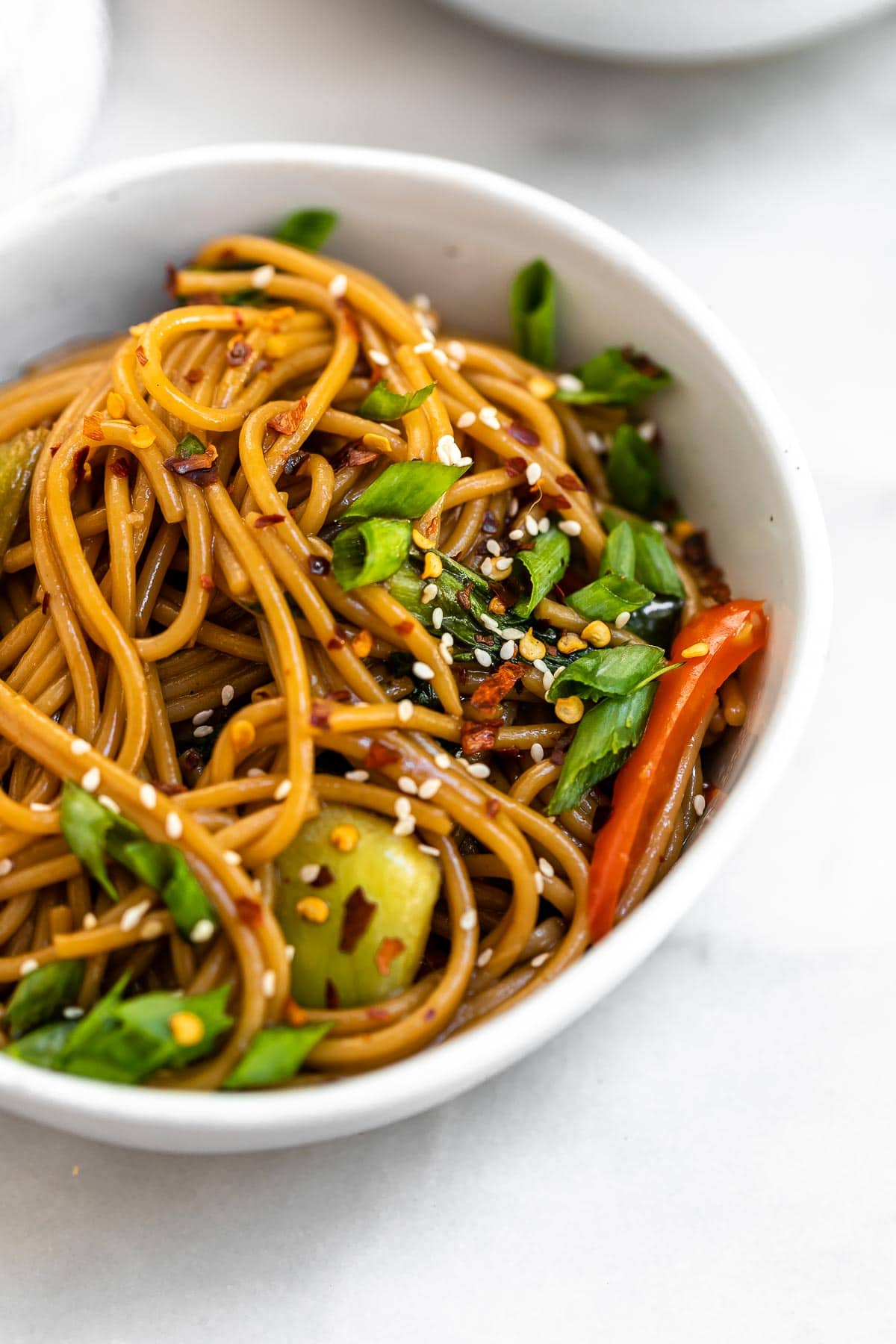 Angled view of the teriyaki noodles with sesame seeds on top.