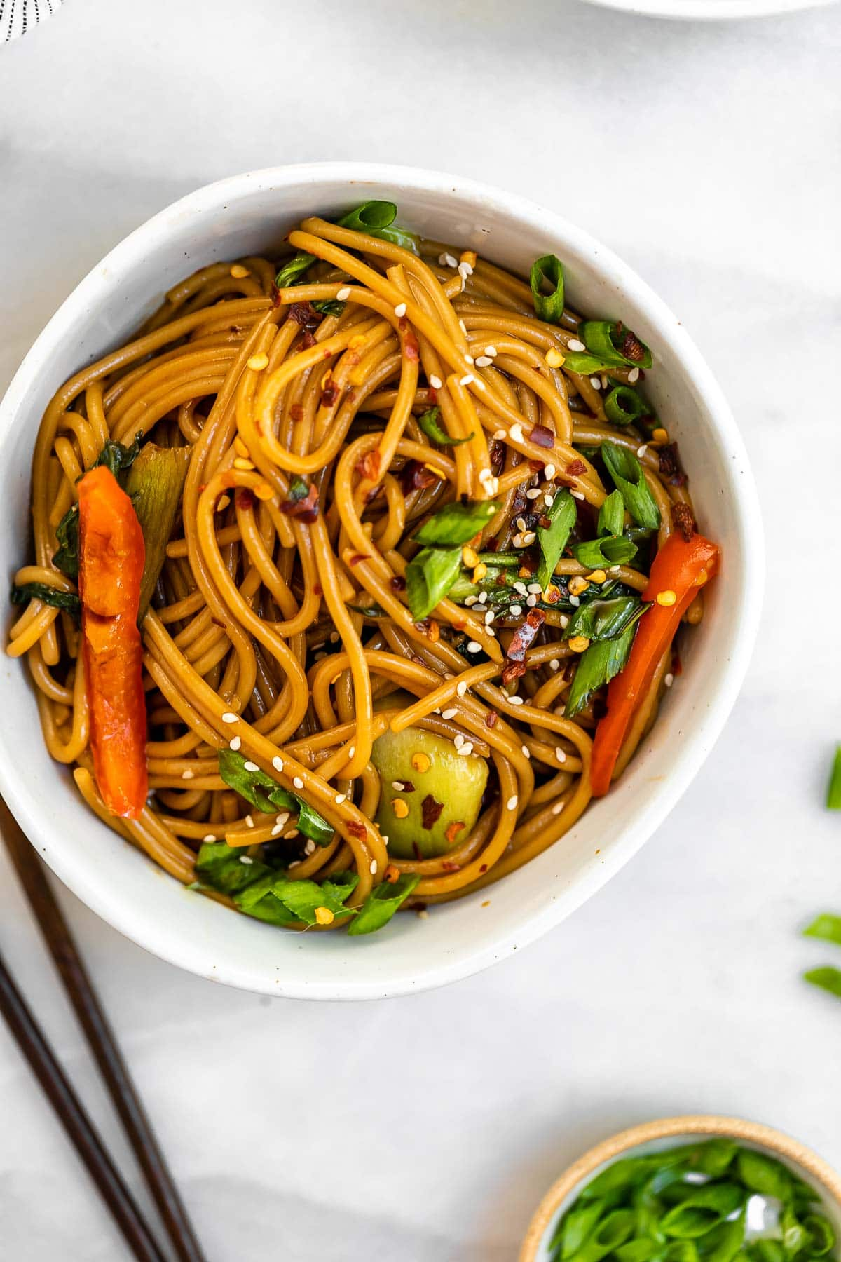 Teriyaki noodles with veggies in a small bowl.