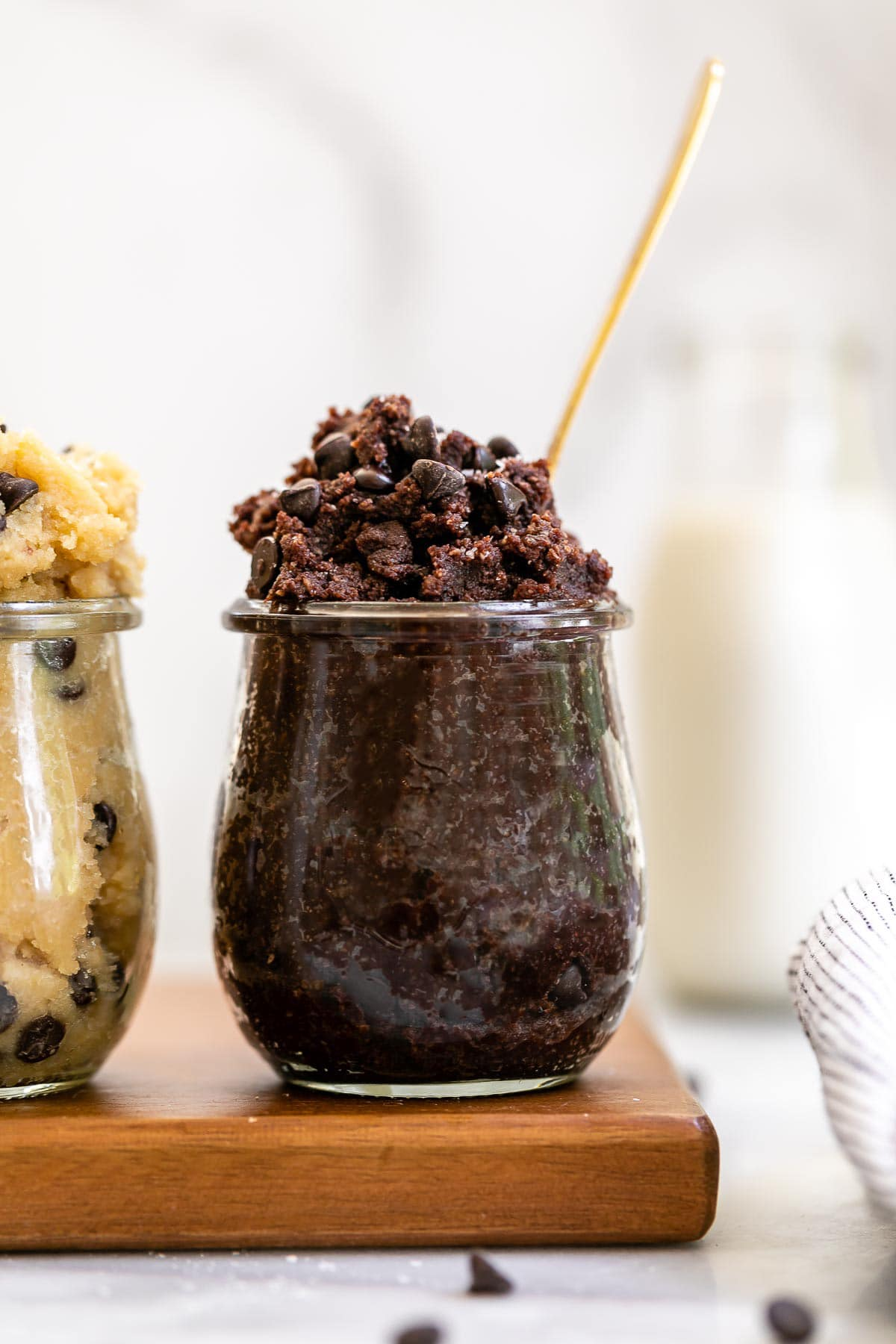Vegan cookie dough in a jar with a spoon coming out.