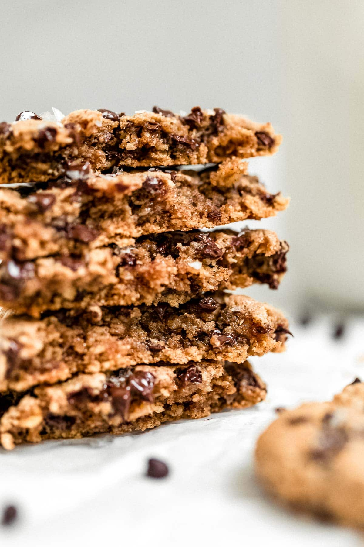 Vegan oatmeal chocolate chip cookies stacked on each other with milk in the background.