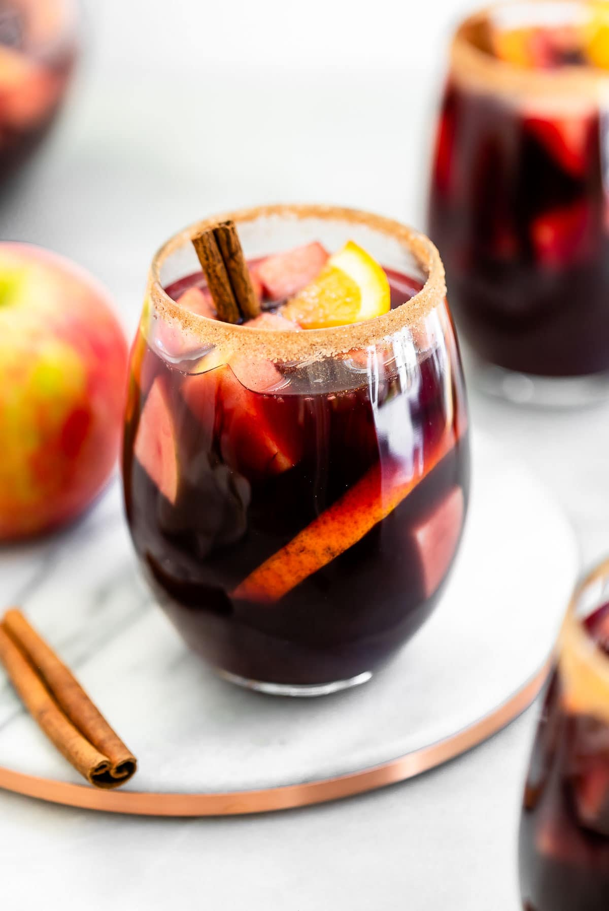 Three glass of fall sangria on a marble board.